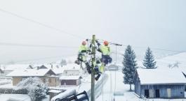 Electricien de réseau suspendu à un poteau électrique en hiver