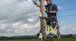 Electricien de réseau suspendu à un poteau électrique